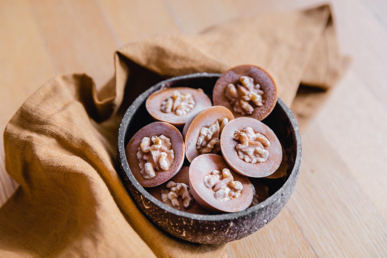 Gefrorene Kürbis Schoko Bites mit Walnüssen in einer Kokosschale