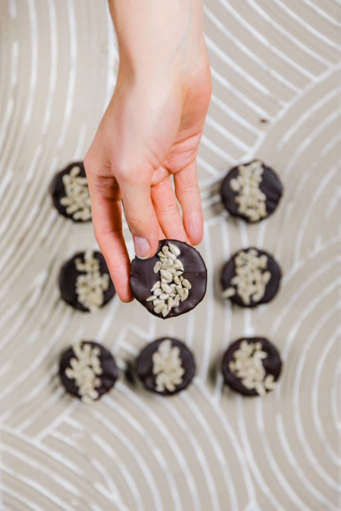 rohveganer snack in reese's form. bestehend aus zwei schichten: cashews und sonnenblumenkernmus. überzogen mit schokolade und mit sonnenblumenkernen dekoriert